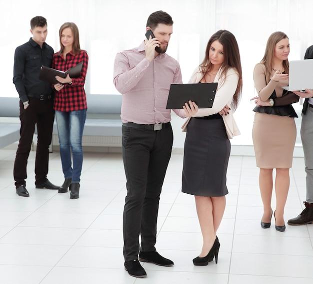 Personas que esperan una entrevista de trabajo en el pasillo de la oficina.