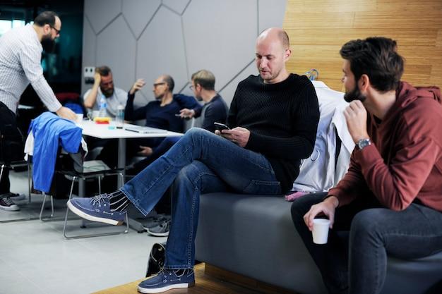 Las personas que esperan se relajan en la sala de café durante el descanso