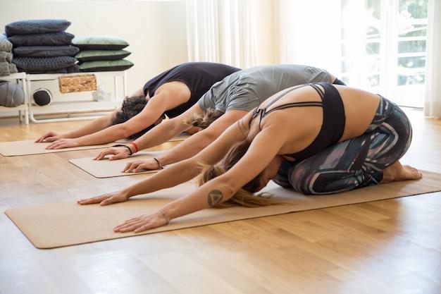 Las personas que hacen al niño posan en colchonetas en la clase de yoga