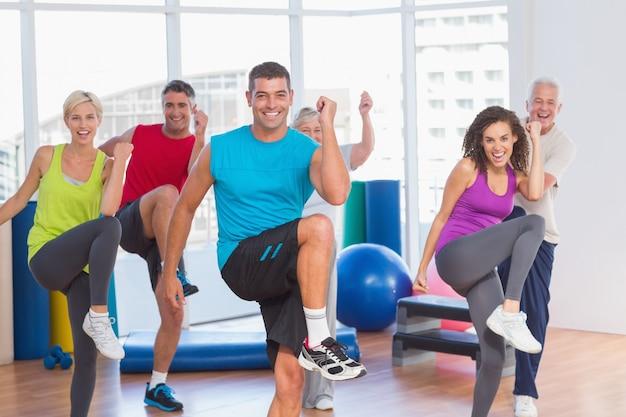 Personas que hacen ejercicio físico de poder en la clase de yoga