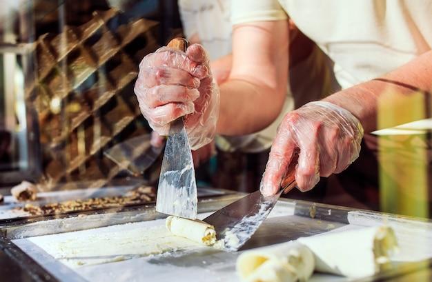 Las personas que hacen rollos de helado frito en una sartén de congelación.