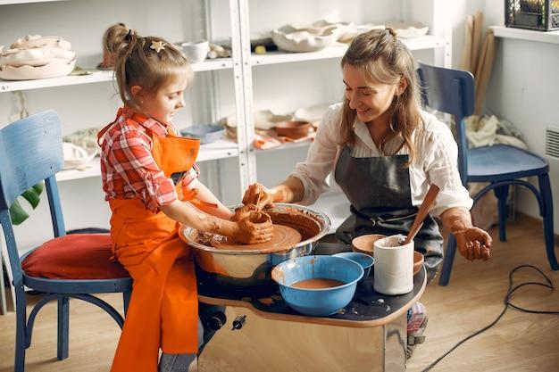 Las personas que hacen una vasija de arcilla en una máquina de alfarería