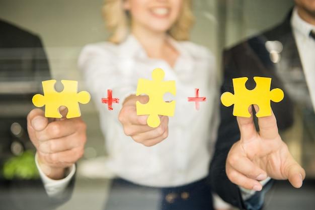 Personas que intentan conectar pequeñas piezas de rompecabezas.