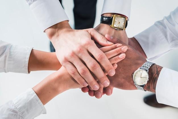Las personas que ponen las manos apiladas prometen ayuda y apoyo contra el fondo blanco