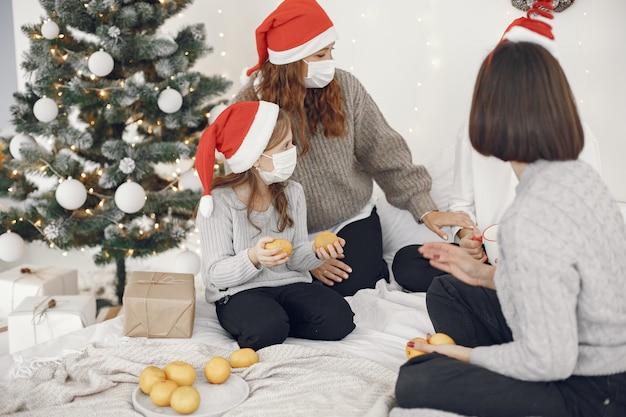 Personas que se preparan para navidad. dos madres jugando con sus hijos. hora del coronavirus. aislamiento.