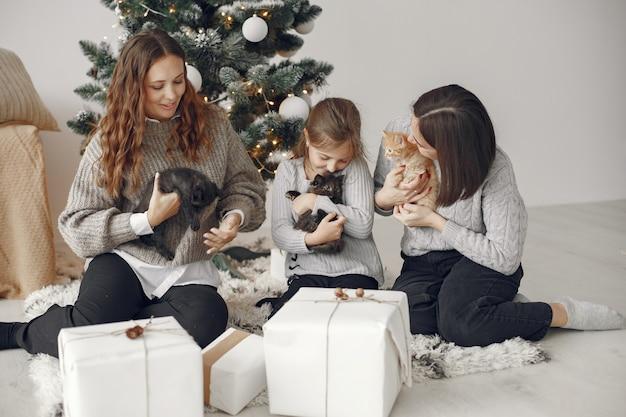 Personas que se preparan para navidad. gente sentada junto al árbol de navidad.