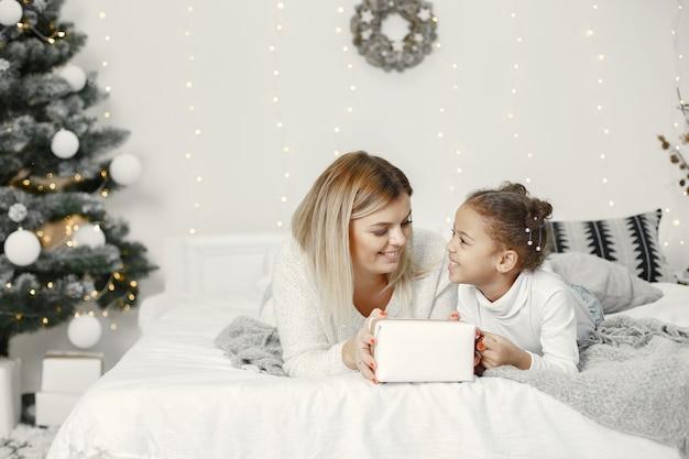 Personas que se preparan para navidad. madre jugando con su hija. la familia está descansando en una sala festiva. niño en un suéter suéter.