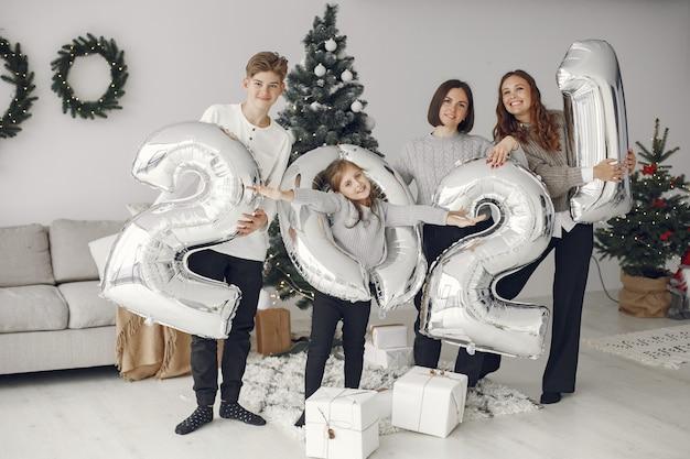 Personas que se preparan para navidad. personas con globos 2021 / familia descansando en una sala festiva.