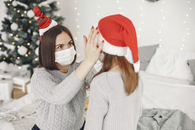 Personas que se preparan para navidad. tema de coronavirus. madre jugando con su hija. niño con un suéter gris.