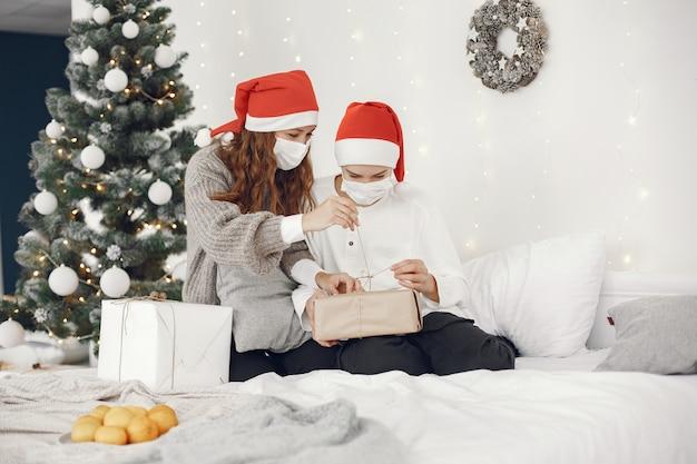 Personas que se preparan para navidad. tema de coronavirus. madre jugando con su hijo. chico con un suéter blanco.