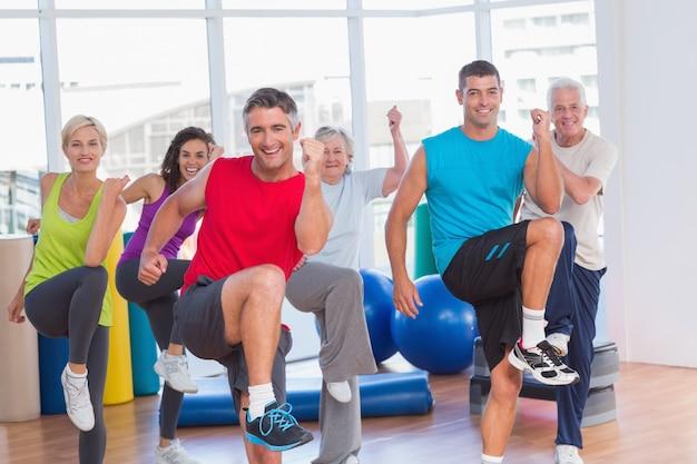 Personas que realizan ejercicios aeróbicos en clase de gimnasia