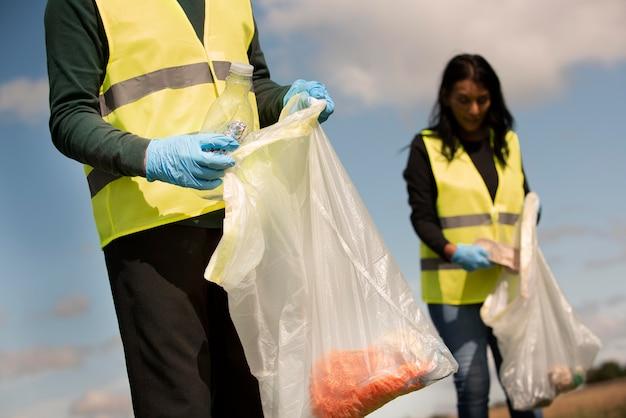 Personas que realizan servicio comunitario recogiendo basura al aire libre.