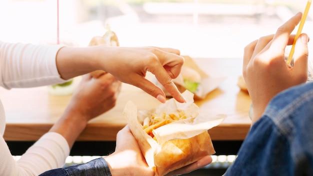 Personas que tienen comida rápida con papas fritas