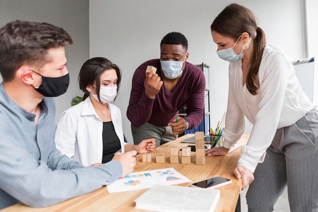 Personas que tienen una reunión en la oficina con máscaras puestas durante la pandemia