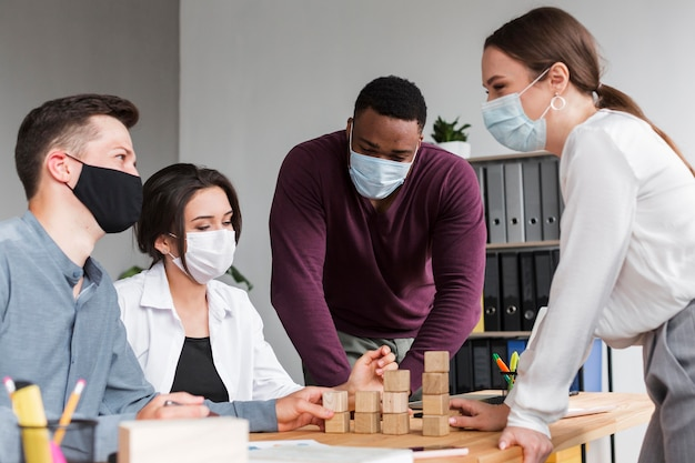 Personas que tienen una reunión en la oficina durante una pandemia con máscaras