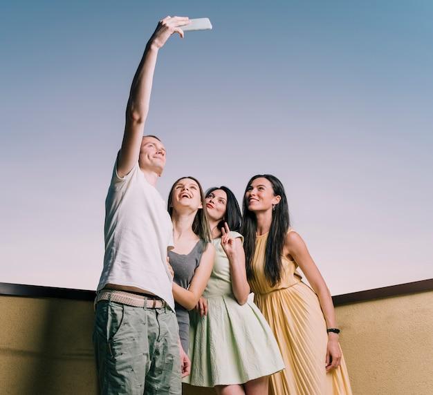 Las personas que toman selfie en la azotea desde abajo