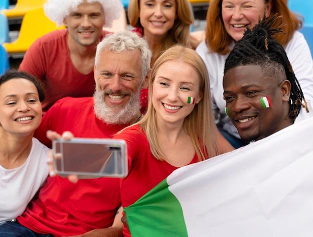 Personas que se toman una selfie en un partido de fútbol.