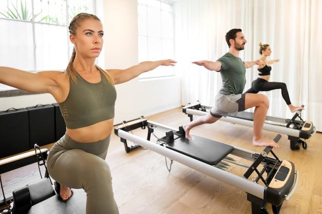 Personas que trabajan haciendo ejercicios de estocada de yoga