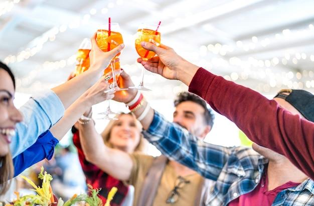 Las personas que tuestan la bebida spritz en el moderno bar de cócteles - enfoque selectivo en cócteles