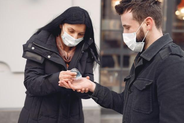Las personas que usan una máscara protectora de pie en la calle mientras usan gel de alcohol