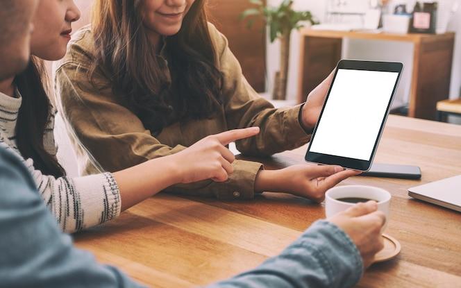 Las personas que usan y miran la misma maqueta tablet pc en una mesa de madera juntas