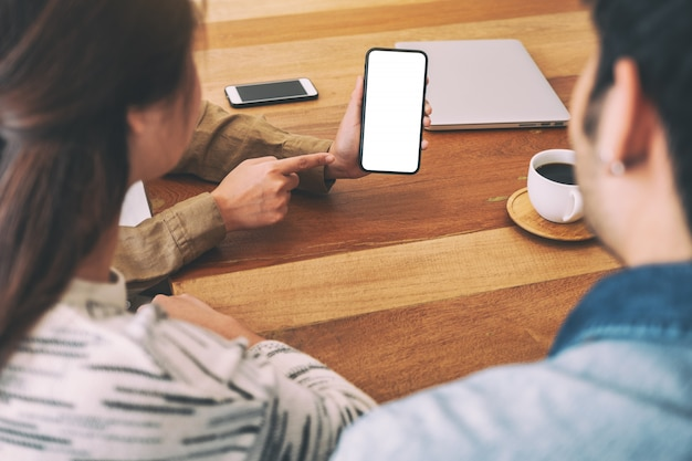 Las personas que usan y miran el mismo teléfono móvil maqueta en una mesa de madera juntos