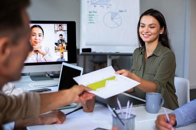 Personas que utilizan dispositivos digitales durante una reunión