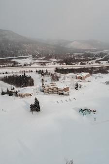 Las personas que viajan en el remonte de nieve en el campo cubierto de nieve durante el día
