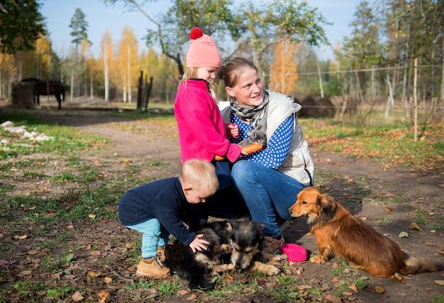 Personas reales de la familia, niños y adultos con muchas mascotas se divierten al aire libre