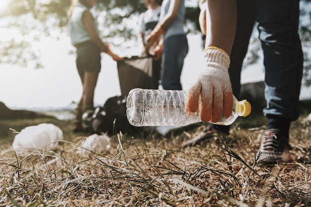 Personas recogiendo basura y poniéndola en una bolsa negra de plástico para limpiar