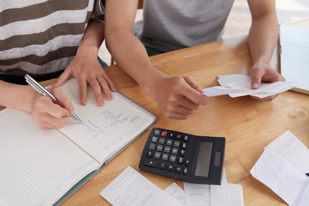 Personas recortadas irreconocibles que mantienen registros de gastos