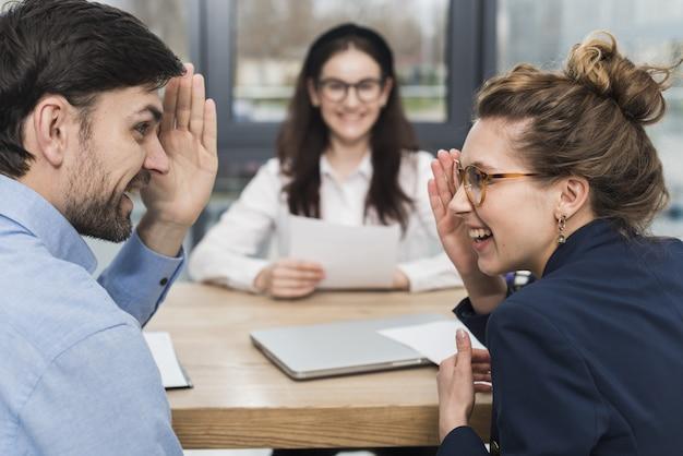 Personas de recursos humanos que hablan de una mujer que asiste a una entrevista de trabajo