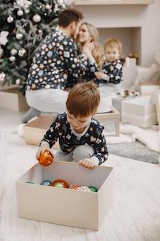 Personas reparando para navidad. gente jugando con niño. la familia está descansando en una sala festiva.
