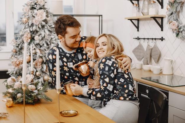 Personas reparando para navidad. gente jugando con su hija. la familia está descansando en una cocina festiva.