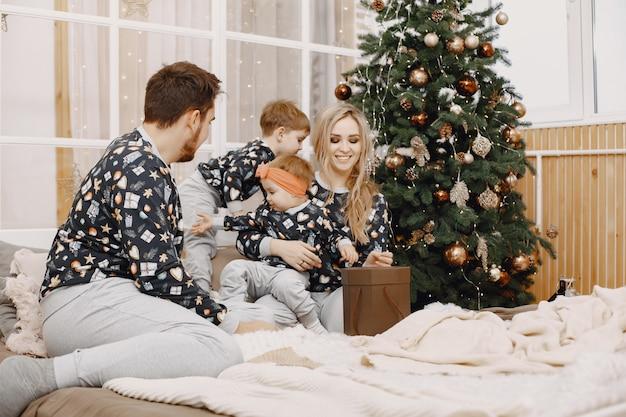 Personas reparando para navidad. gente sentada en una cama. la familia está descansando en una sala festiva.