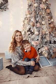 Personas reparando para navidad. madre jugando con su hijo.