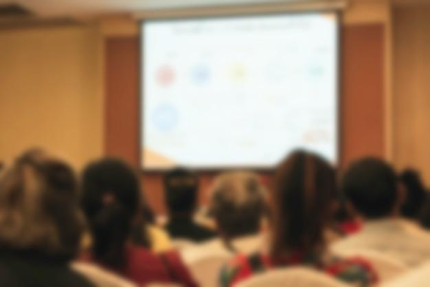 Personas en la reunión o sala de conferencias borrosa para el fondo.