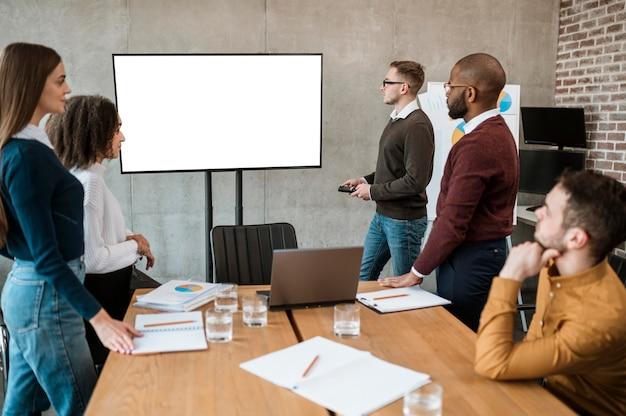 Personas durante una reunión que muestran una presentación.