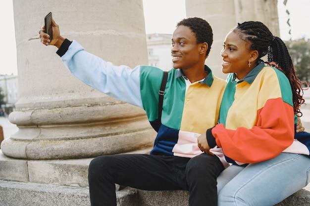 Personas con ropa de identificación. pareja africana en la ciudad de otoño. gente sentada en una calle.