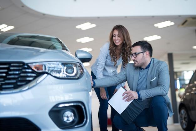 Personas en la sala de exposición del concesionario de automóviles discutiendo sobre vehículo nuevo