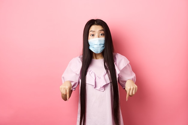Personas sanas y concepto de pandemia de covid-19. chica asiática emocionada en mascarilla apuntando con el dedo hacia abajo, mostrando publicidad con interés, de pie contra el fondo rosa.