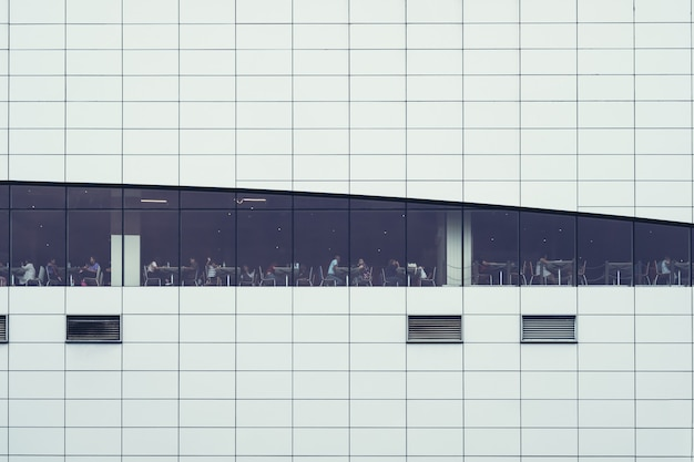 Personas sentadas en cantina del edificio supperstore. interior de ventanas. concepto de empleo, negocios, corporativo, relax, gente de negocios, vida moderna, gente ocupada