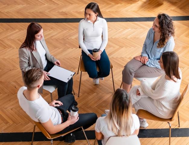 Personas sentadas en círculo de plano medio