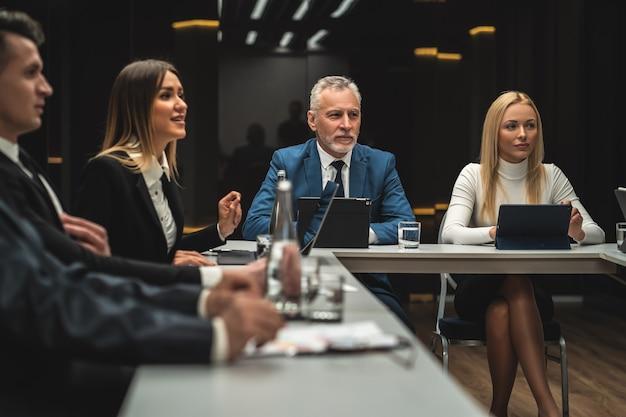 Las personas sentadas a la mesa en la conferencia de negocios.