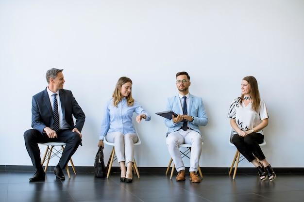 Personas sentadas en la sala de espera antes de una entrevista.