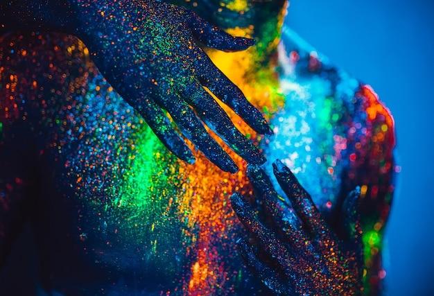 Las personas son polvos fluorescentes de colores. una pareja de enamorados bailando en una discoteca.