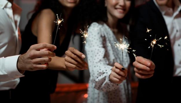 Personas sosteniendo bengalas en la fiesta de fin de año