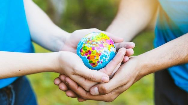 Personas sosteniendo esfera juntos