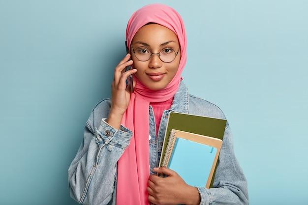 Personas, tecnología, etnia, concepto de comunicación. chica guapa con hijab musulmán tradicional tiene conversación telefónica con un compañero de grupo, discute un proyecto futuro, sostiene dos cuadernos de espiral, posa en el interior
