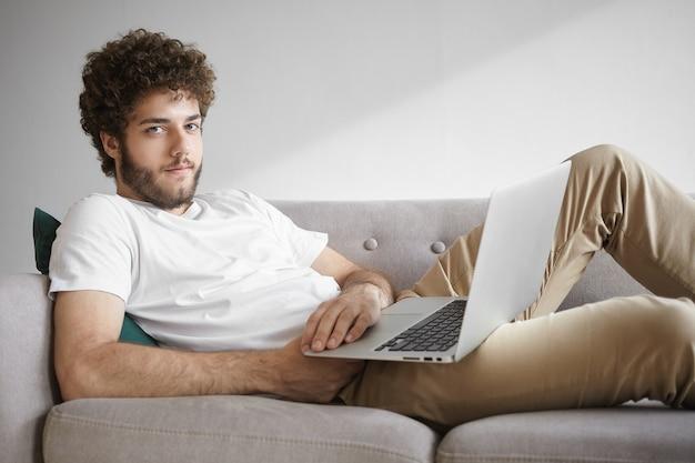 Personas, tecnología moderna y concepto de comunicación. imagen de un chico guapo y elegante con barba sentado en el sofá con una computadora portátil en su regazo, disfrutando de una conexión inalámbrica a internet de alta velocidad